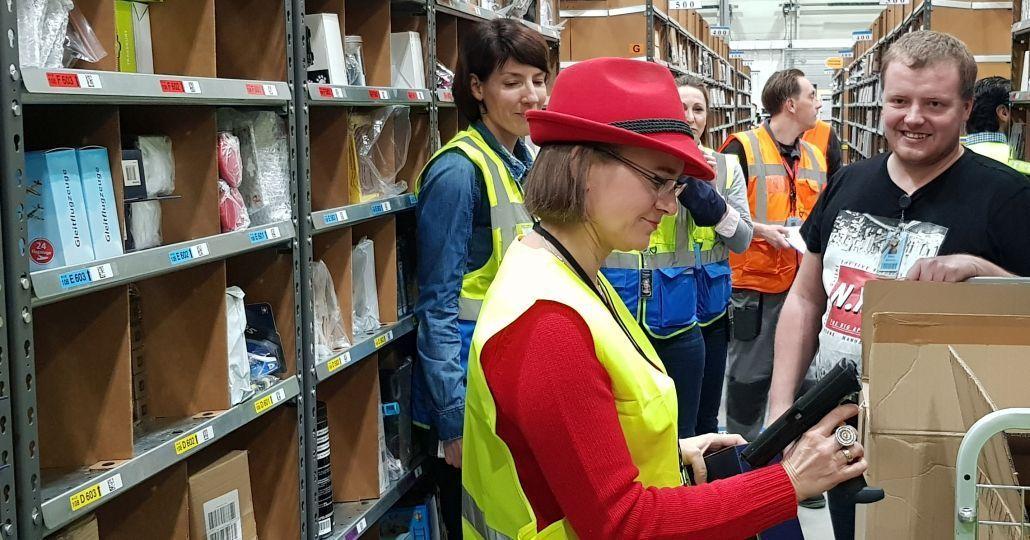 Anke Domscheit-Berg füllt Regale mit Ware auf, hat einen Scanner in der Hand, um den Standort ins System einzupflegen.