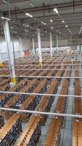 Bild zeigt die Logistik Halle von oben. Regale soweit man sehen kann.