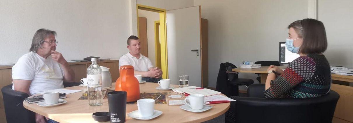 Anke Domscheit-Berg unterhält sich mit 3 Menschen an einem Tisch