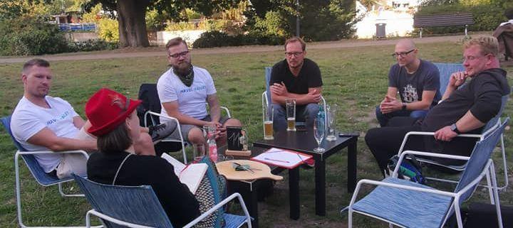 Menschengruppe sitzt im Grünen um kleine Tische