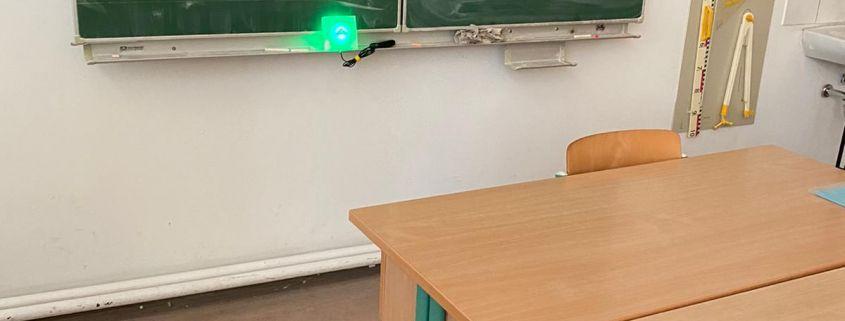 Klassenzimmer mit grüner Tafel, Tischen und Stühlen. Auf der Tafel leuchtet CO2-Ampel grün.