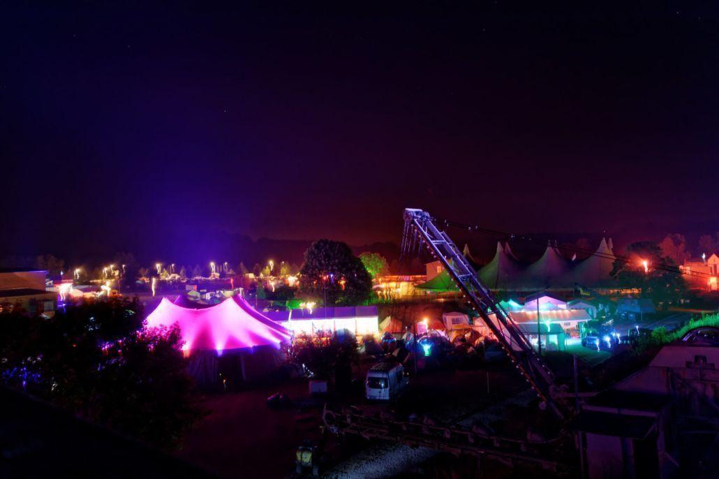 """CCCamp 2015 im Ziegeleipark Mildenberg mit seinen in der Nacht von bunten LED-Lichtern erhellten Zelten. Foto: """"CCCamp 2015 (026)"""" by BlinkenArea.org is licensed under CC BY 2.0"""