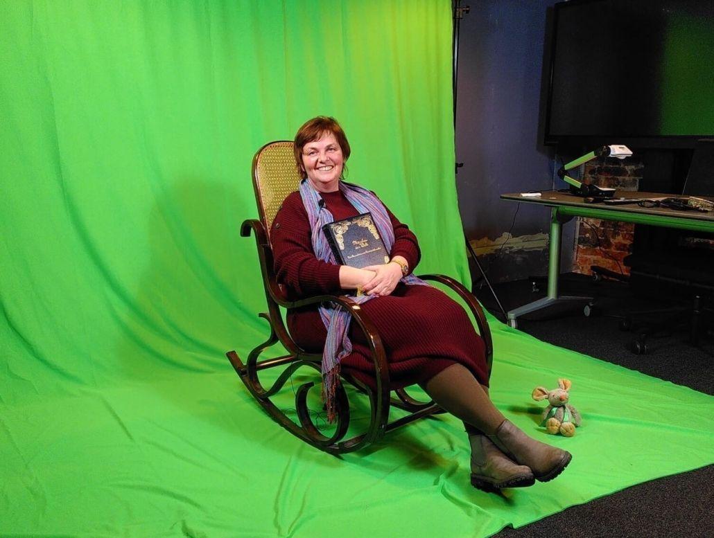 Eine Frau mit Buch in der Hand sitzt lächelnd in einem Schaukelstuhl vor einem grünen Tuch.